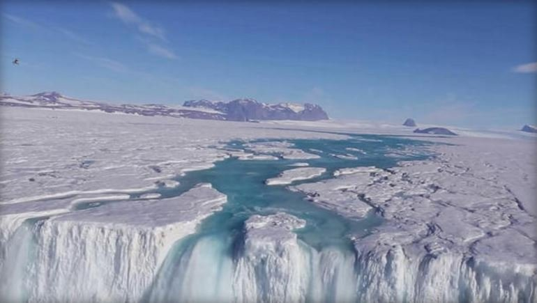 Seen from an aircraft, a 400-foot-wide waterfall drains off the Nansen Ice Shelf into the ocean. WONG SANG LEE/KOREA POLAR RESEARCH INSTITUTE VIA EARTH INSTITUTE/YOUTUBE
