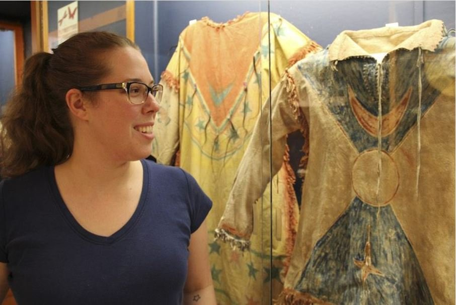 Kathy Barton, the curator at the Yellowstone County Museum, looks at a Ghost Dance shirt owned by a son of Sitting Bull, the Hunkpapa Lakota holy man. (Ed Kemmick/Last Best News)