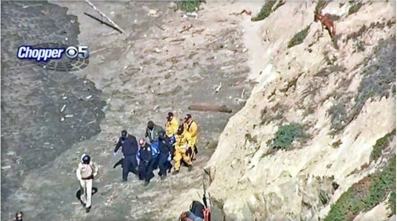 Crews removed a body found below a cliff at Thornton State Beach. A dog, believed to be owned by the victim, can be seen in upper right corner of the frame. / CBS SAN FRANCISCO